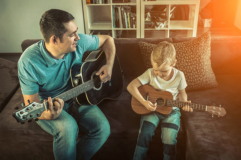 Father teaching his son to play on guitar